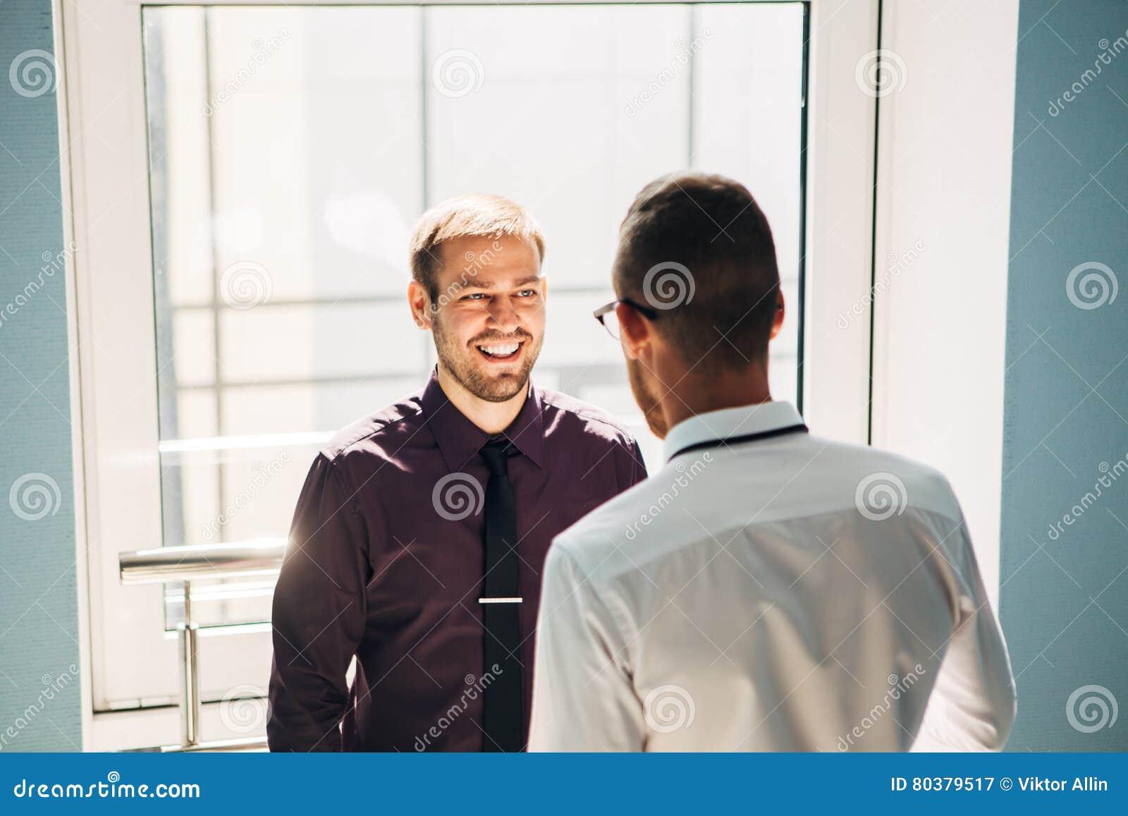 Twee mensen die in de hal van het bureau spreken
