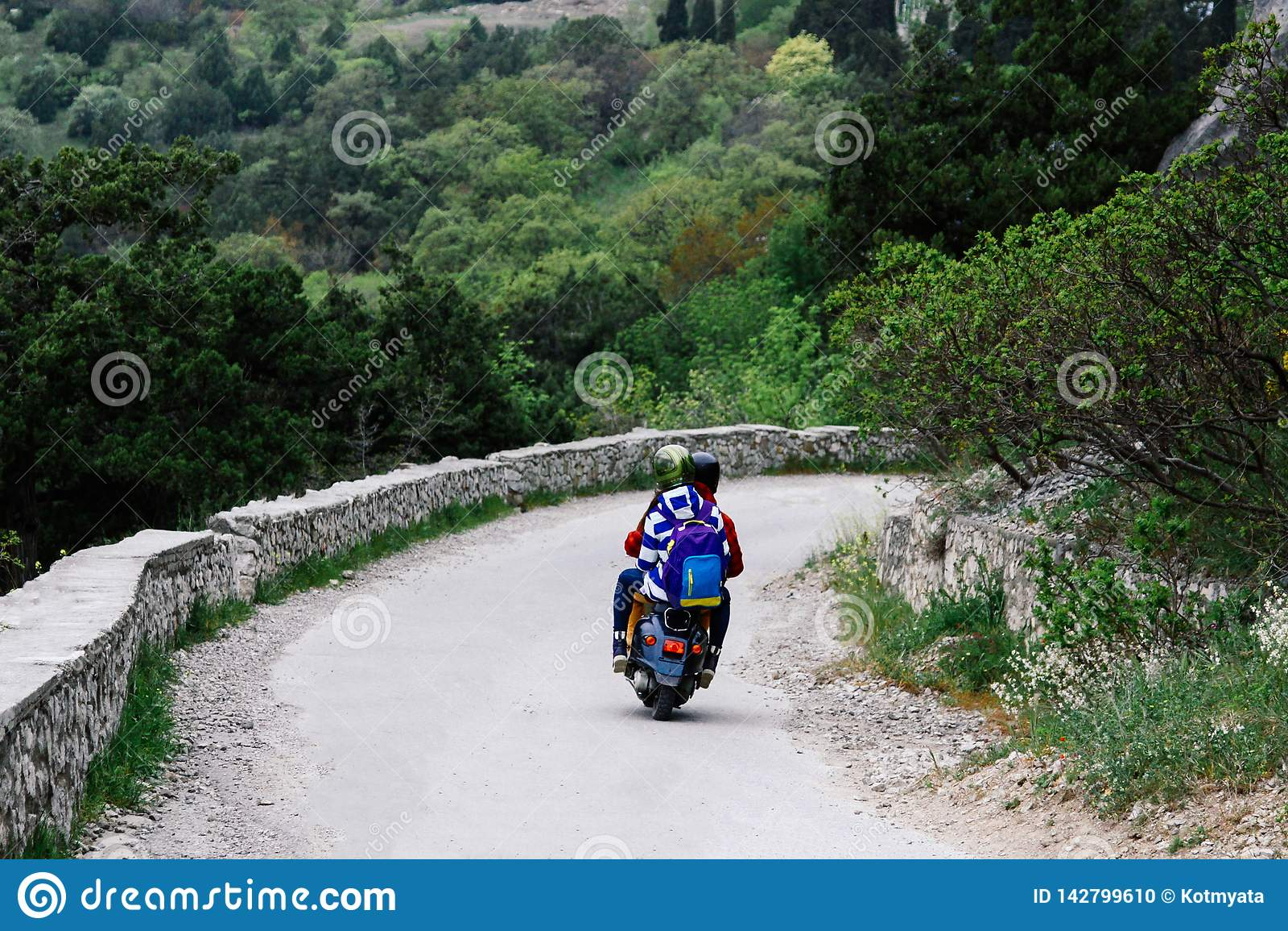 Twee mensen die een bergweg berijden op een uitstekende autoped Conceptueel voor reizigers en minnaars van uitstekende autopedden