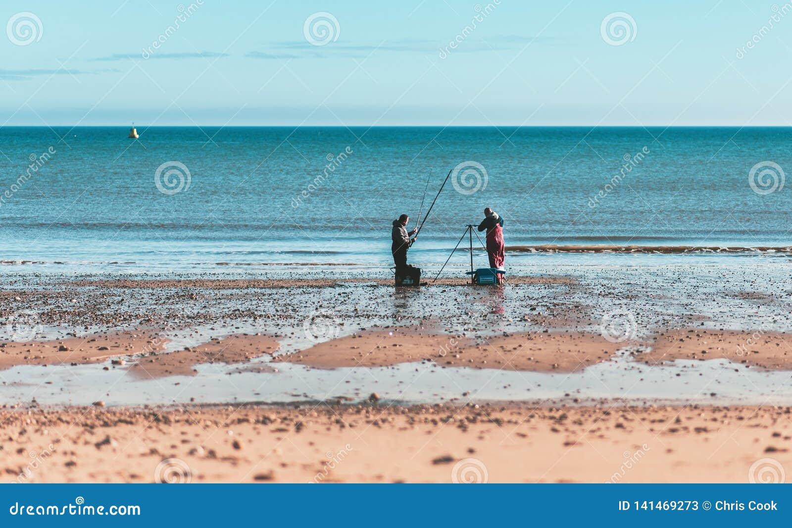 Twee mensen die op Hornsea-Strand vissen