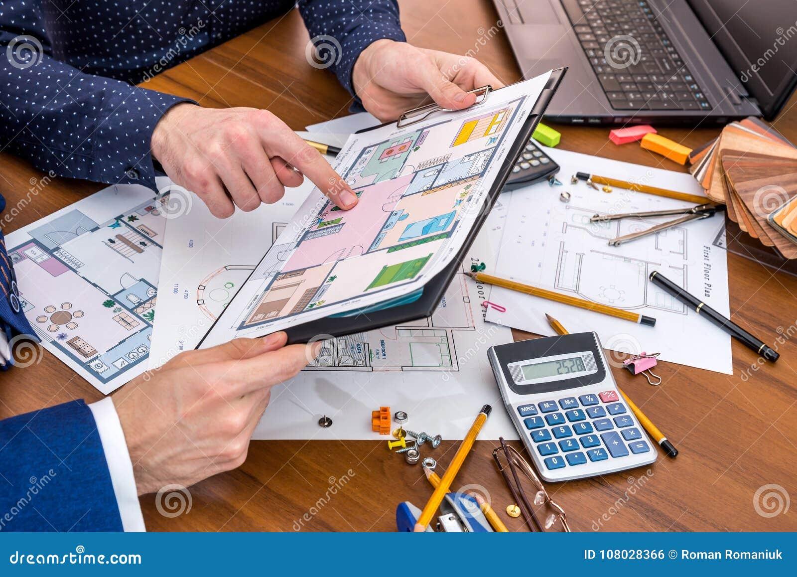 Twee mensen die over architecturaal project met techniekhulpmiddelen op werkplaats spreken