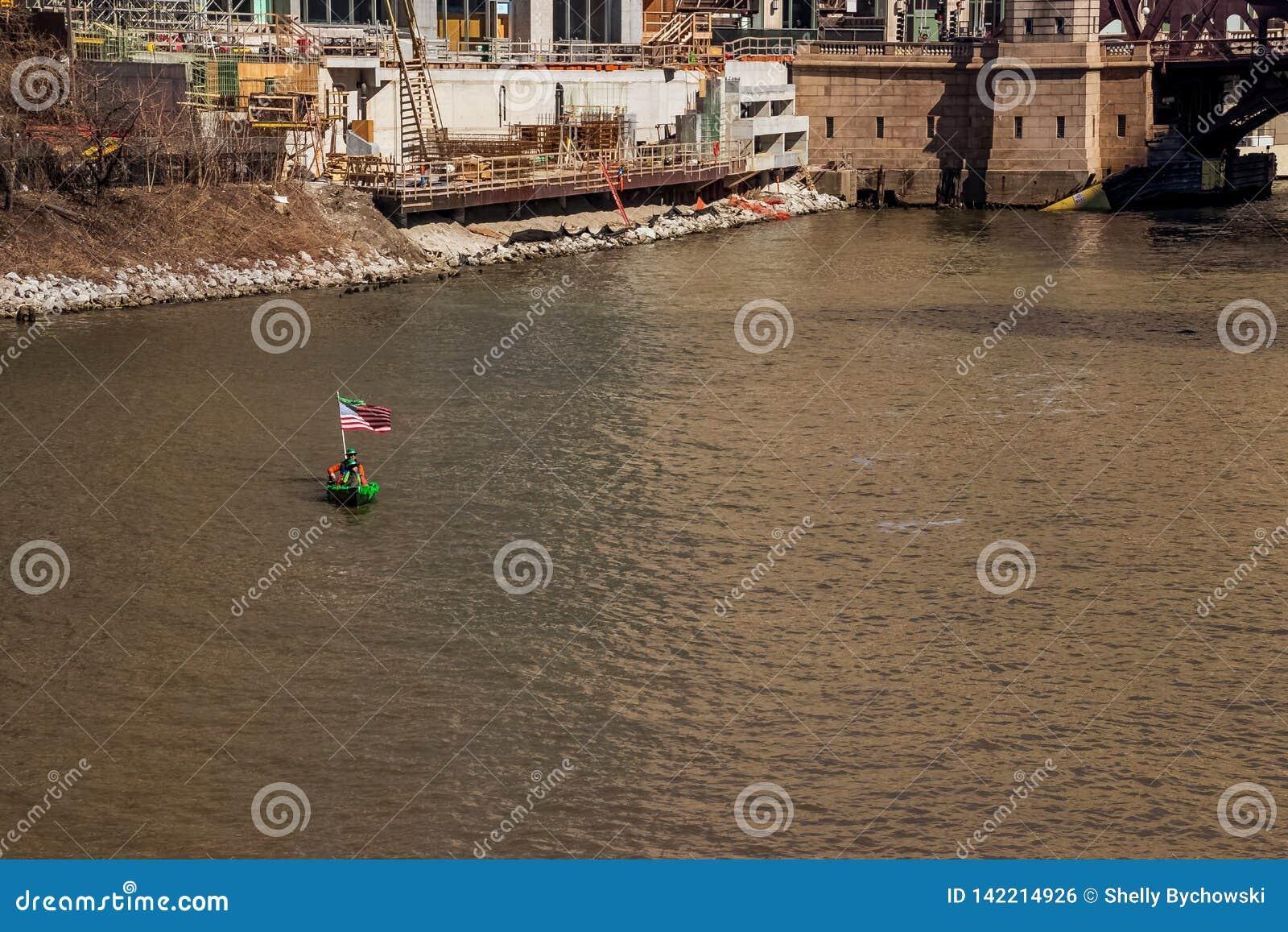 Twee mensen in een St Patricks Dag verfraaiden kano met Amerikaanse vlag aangezien zij door een bouwwerf op de Rivier van Chicago