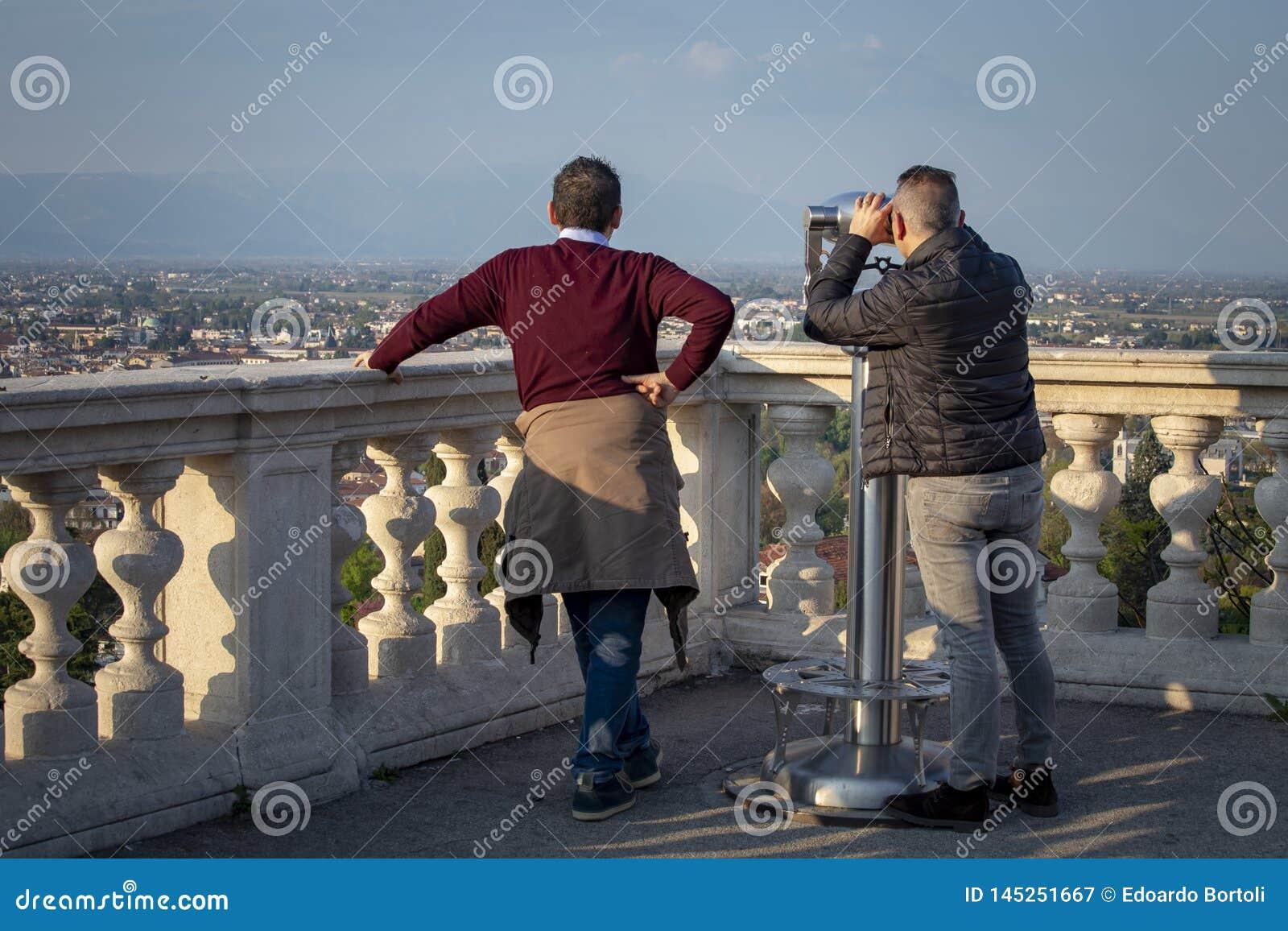 Twee mensen nemen de stad van Vicenza met verrekijkers waar