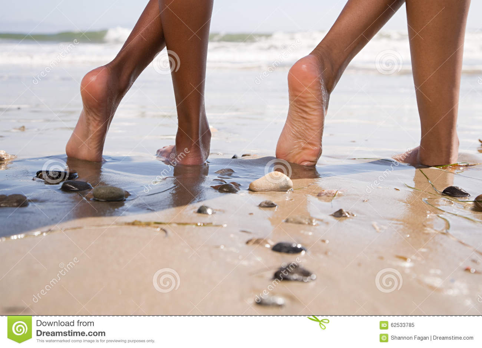 Twee mensen op strand met gekruiste benen stock afbeelding
