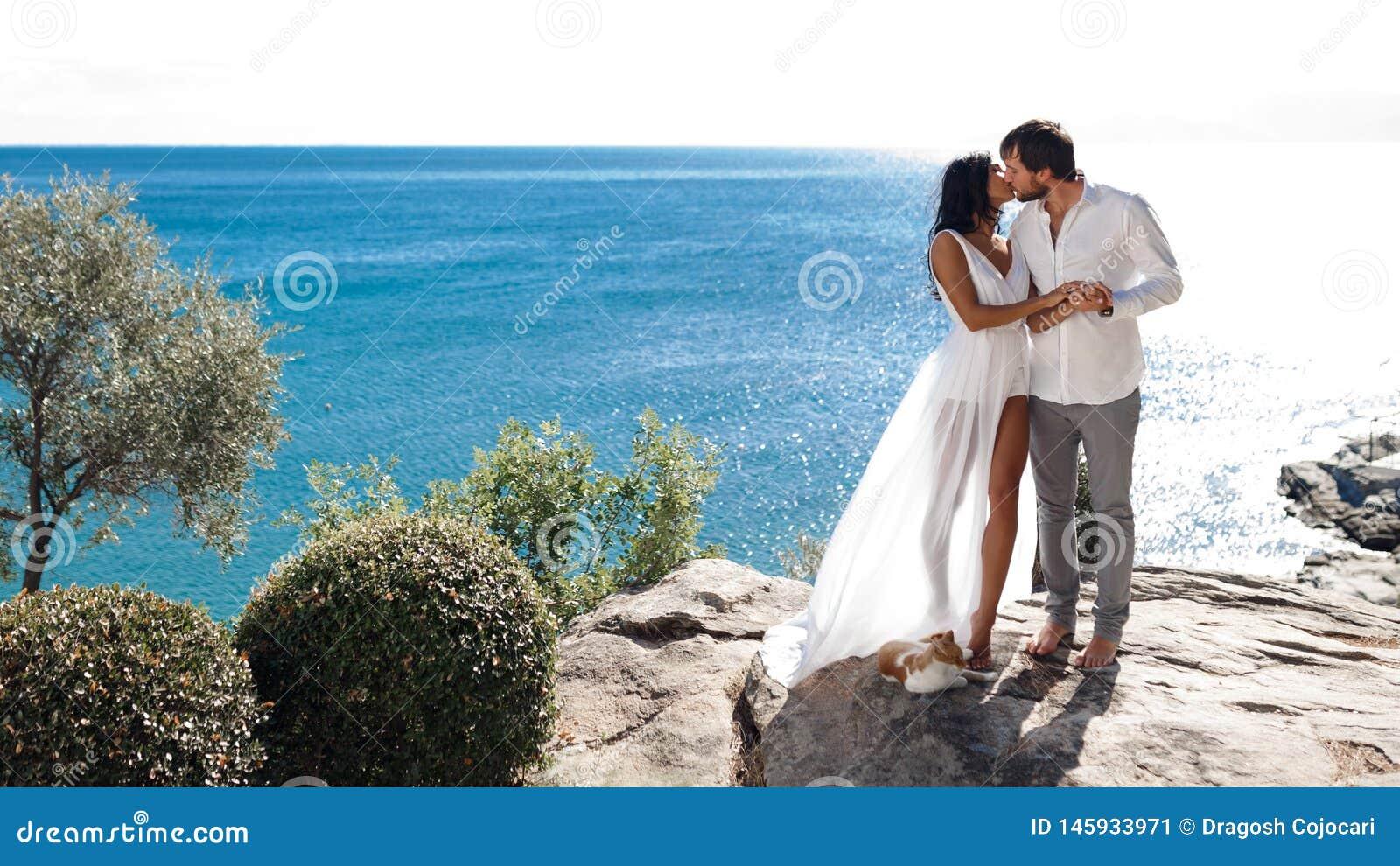 Twee minnaars kussen en omhelzen op een kust achter mediterraan zeegezicht, gehuwde de zomertijd, enkel