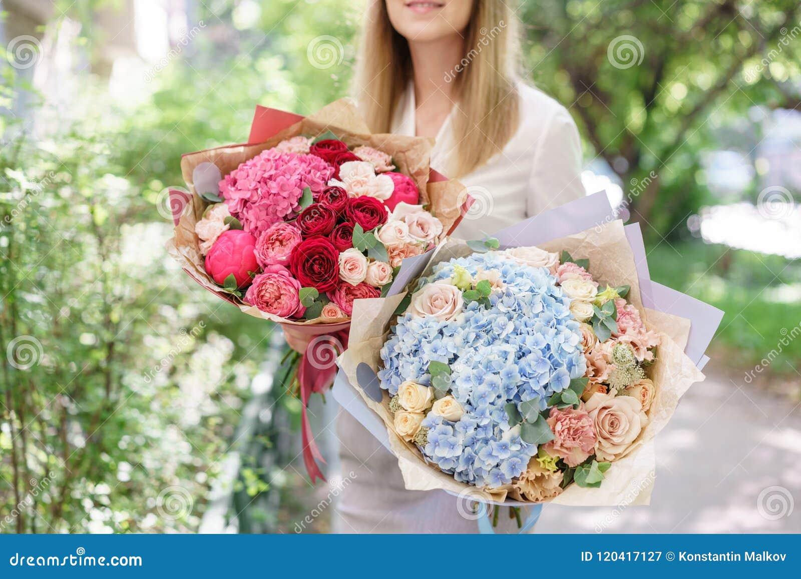 Twee Mooi de zomerboeket Regeling met mengelingsbloemen Jong meisje die een bloemstuk met hydrangea hortensia houden E