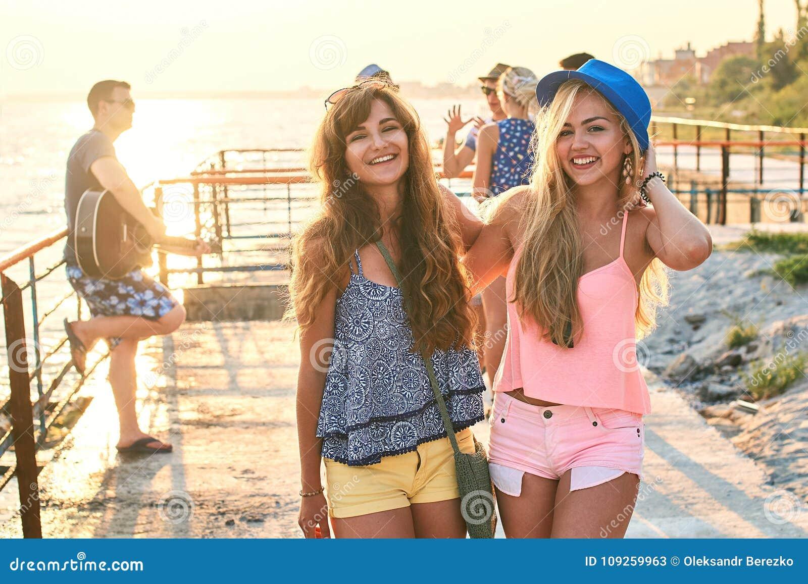 Twee mooie jonge meisjes die pret hebben bij de avondkust met groep hun vrienden op achtergrond