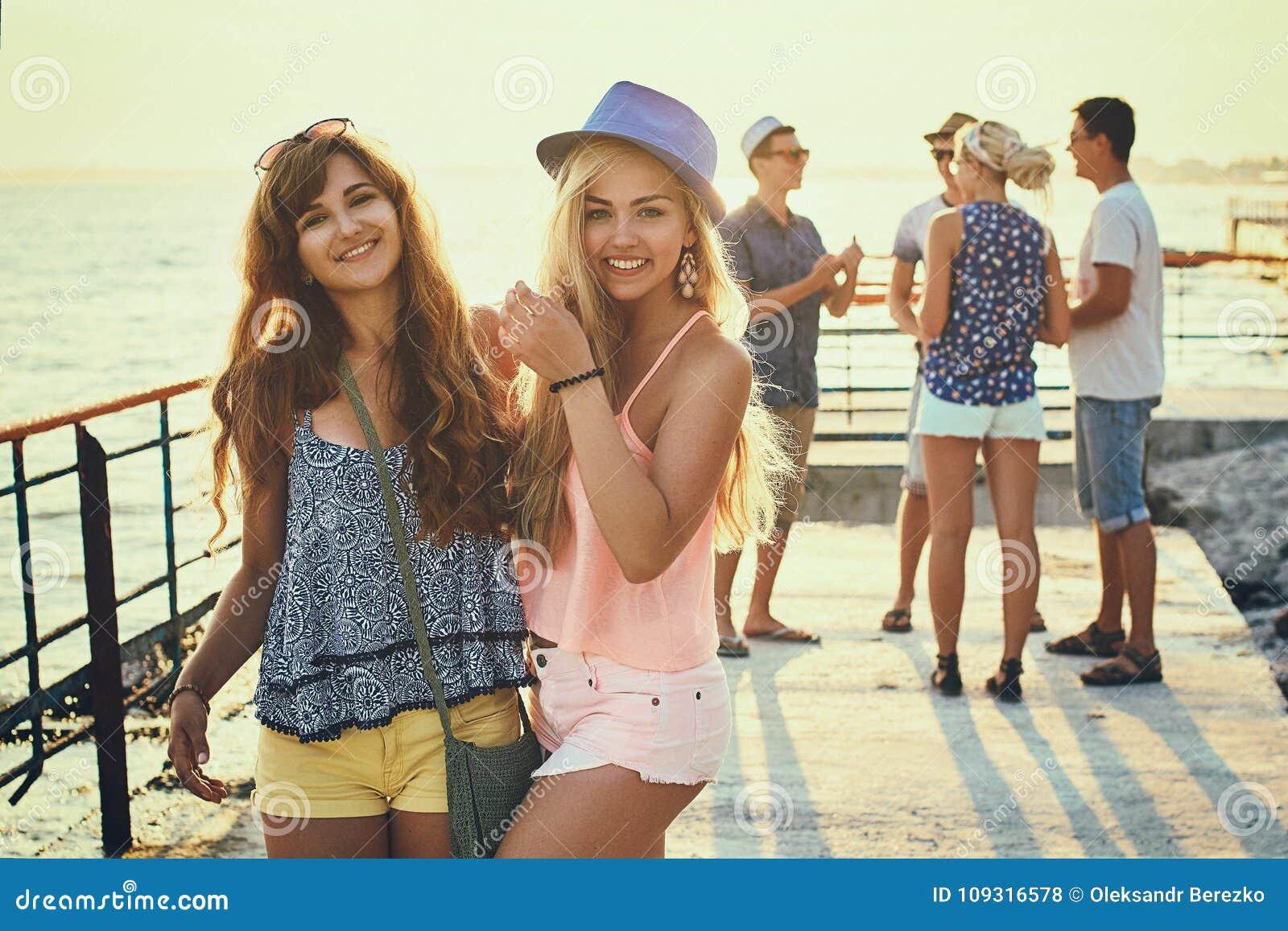 Twee mooie jonge meisjes die pret hebben bij de avondkust met groep hun vrienden op achtergrond stemden in wijnoogst