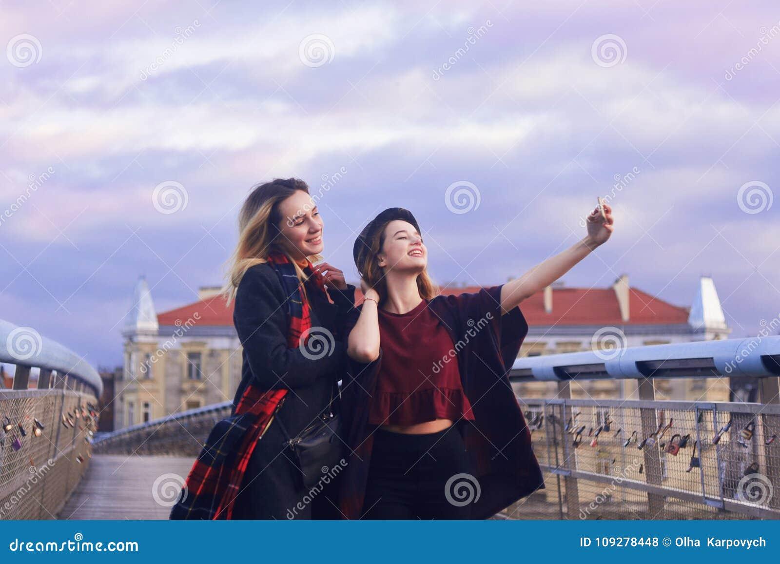 Twee mooie jonge studentenmeisjes die pret hebben die grappige gezichten maken en zelfportretten met Smartphone nemen Vriendschap