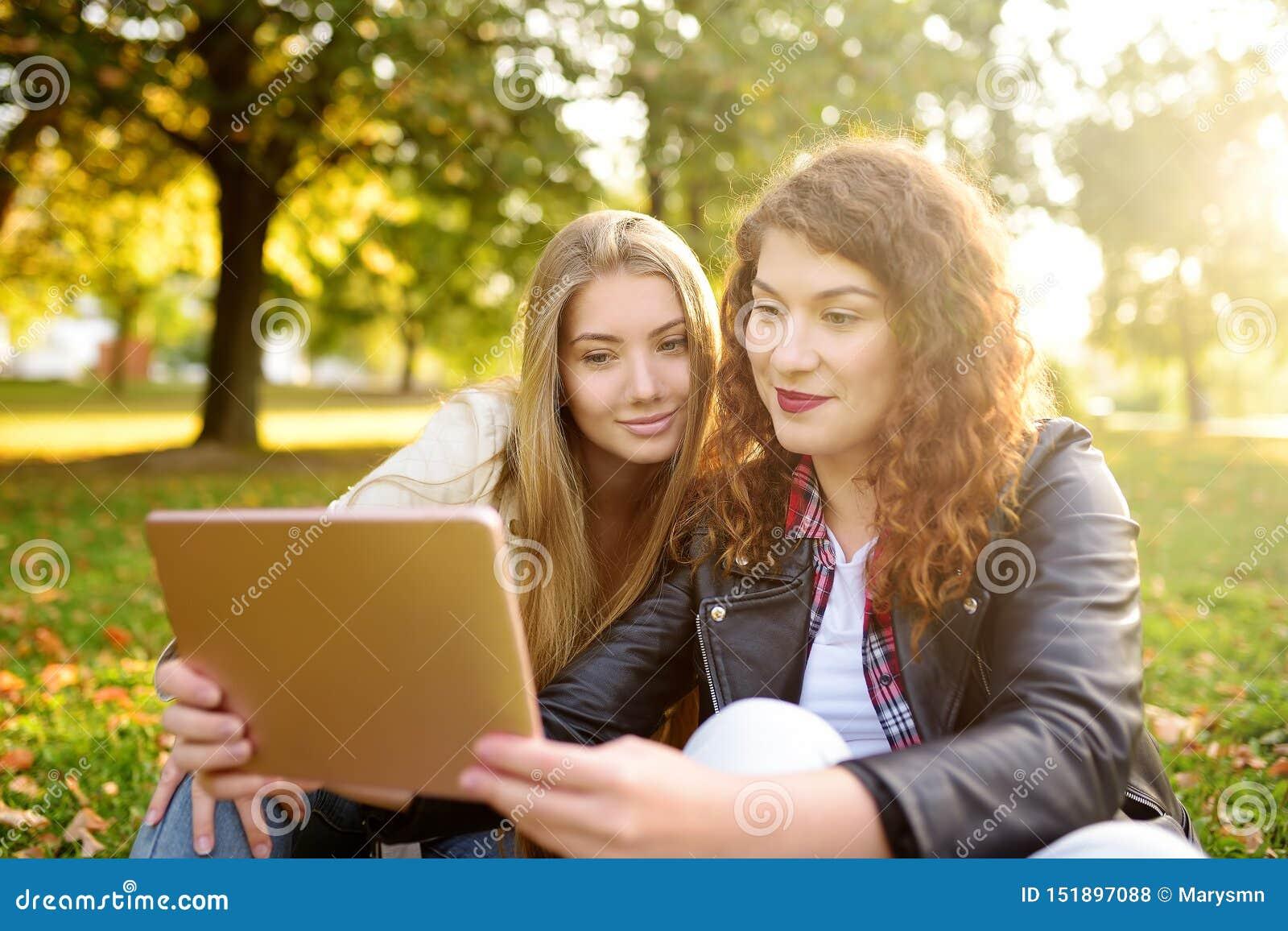 Twee mooie jonge vrouwen die tabletcomputer met behulp van samen bij zonnig park Verre mededeling Het dateren van plaats
