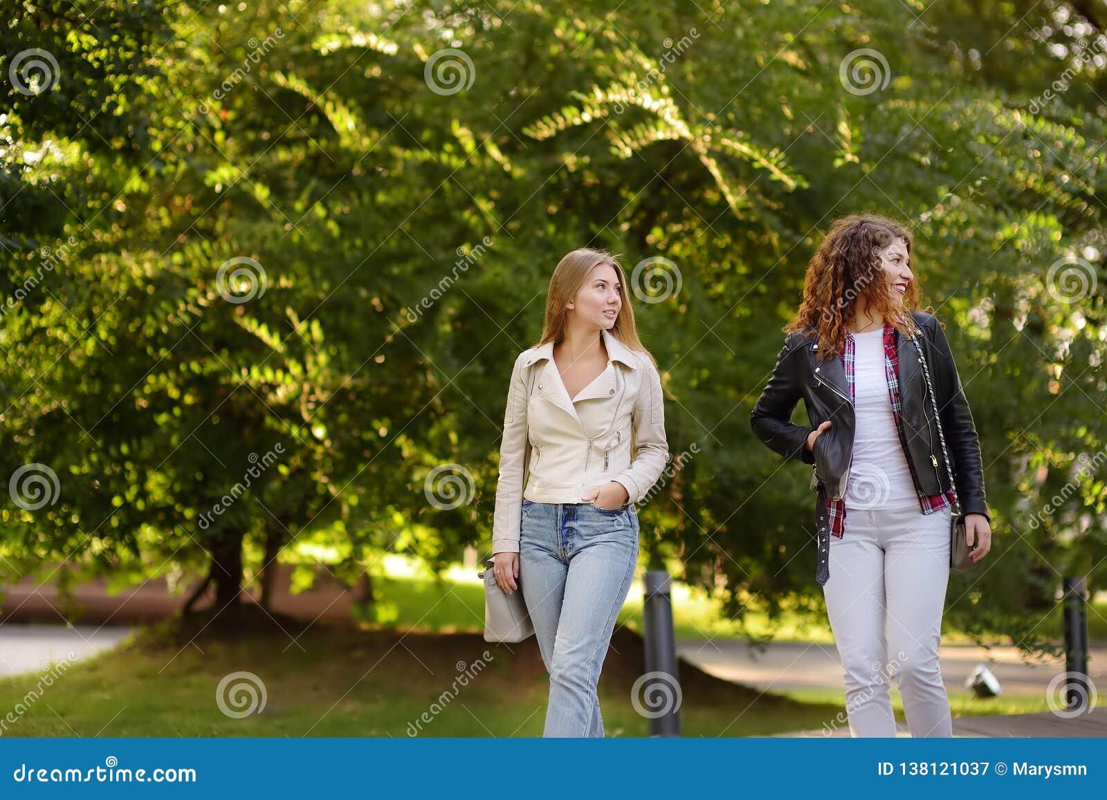 Twee mooie jonge vrouwen die terwijl het lopen in Sunny Park spreken Mededeling en roddel