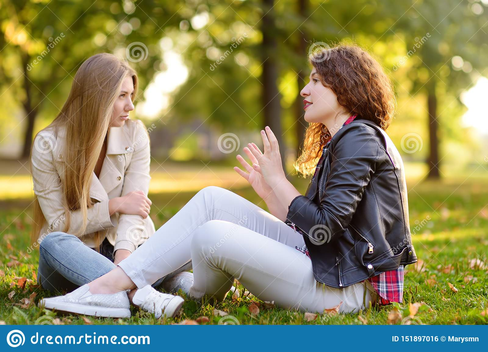 Twee mooie jonge vrouwen die terwijl het zitten op de grond bij zonnig park spreken meisjes