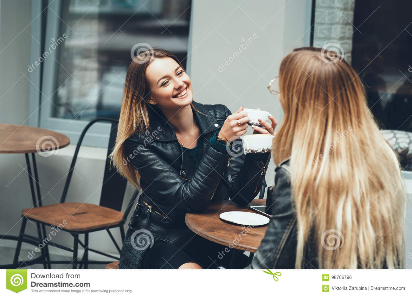 Twee mooie jonge vrouwen in manierkleren die rust het spreken en het drinken koffie in restaurant hebben openlucht