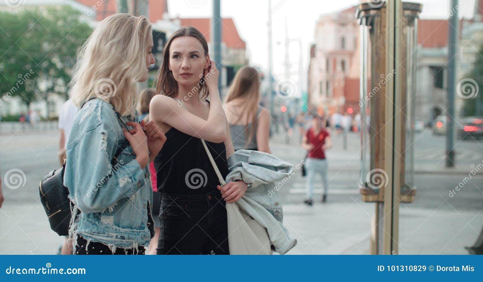 Twee mooie meisjes die kleren in een winkelvenster bekijken
