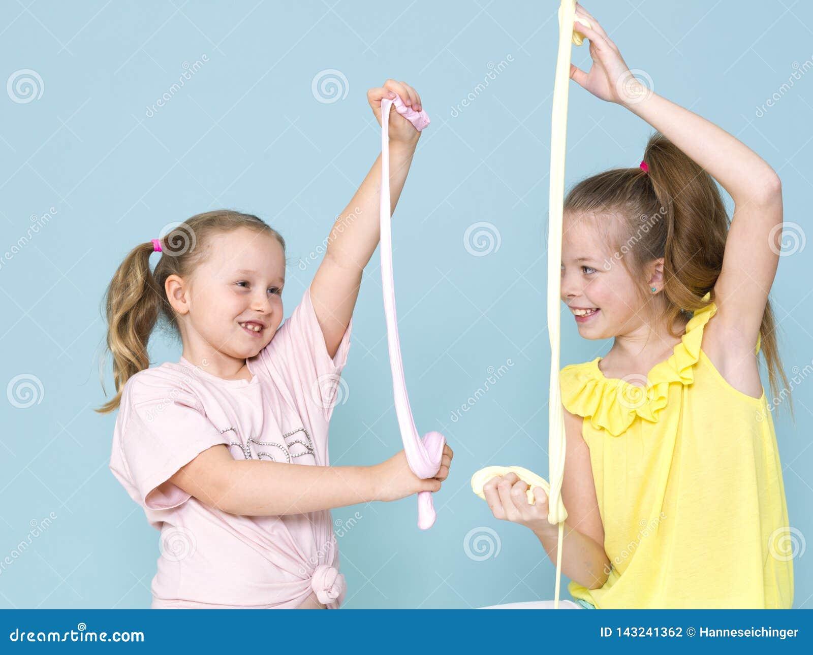Twee mooie meisjes die met eigengemaakt slijm spelen en heel wat pret voor blauwe achtergrond hebben