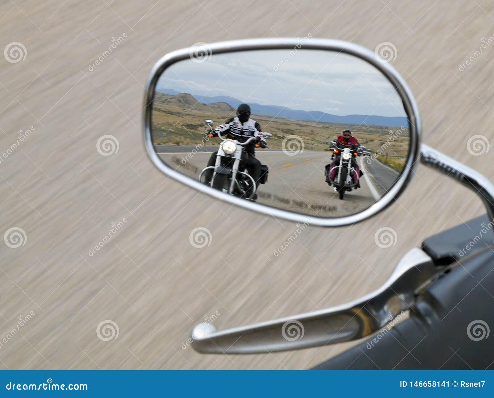Twee motorrijders in de achteruitkijkspiegel