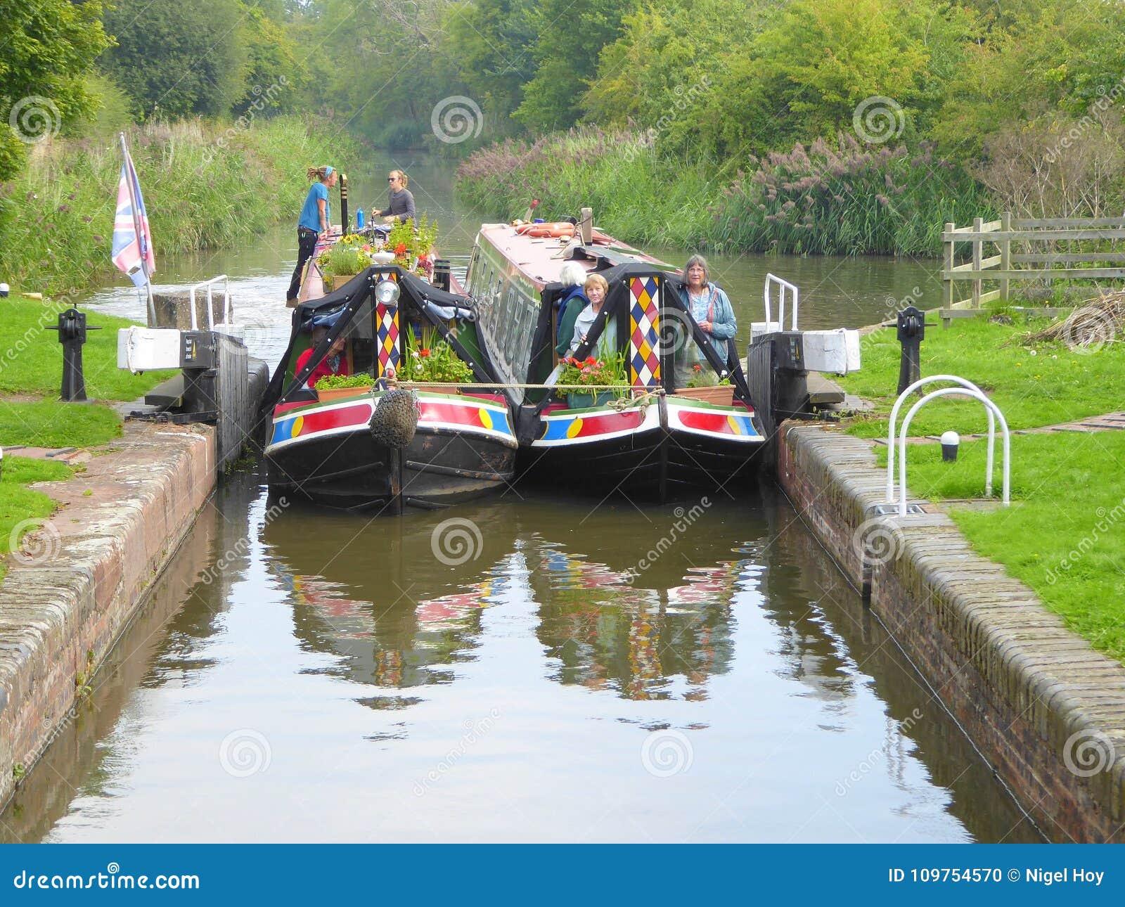 Twee narrowboats die een kanaalslot ingaan