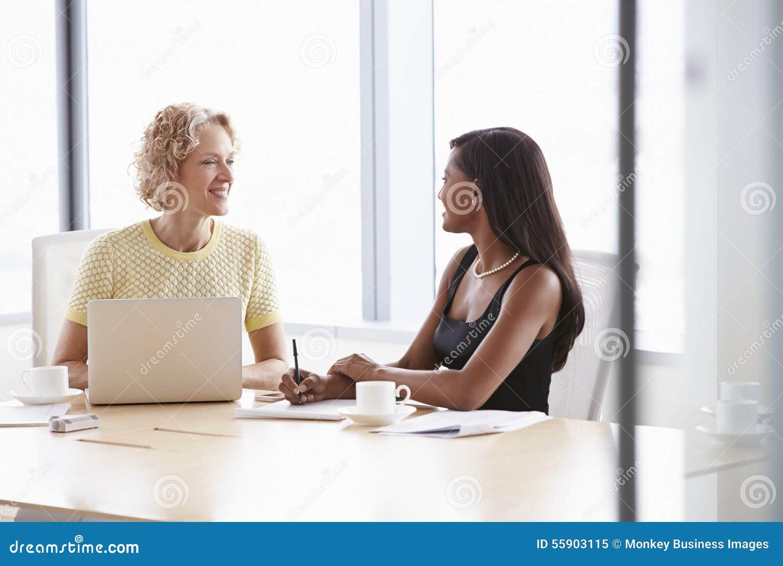 Twee Onderneemsters die aan Laptop in Bestuurskamer samenwerken