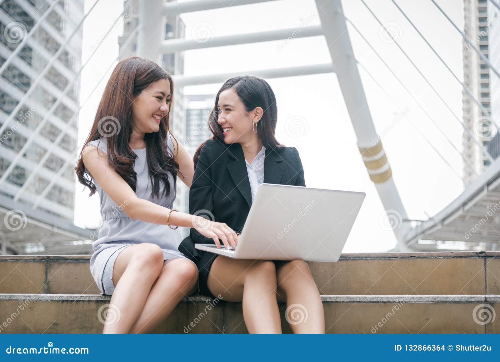 Twee onderneemsters die aan laptop computer met gelukkige grappige em werken