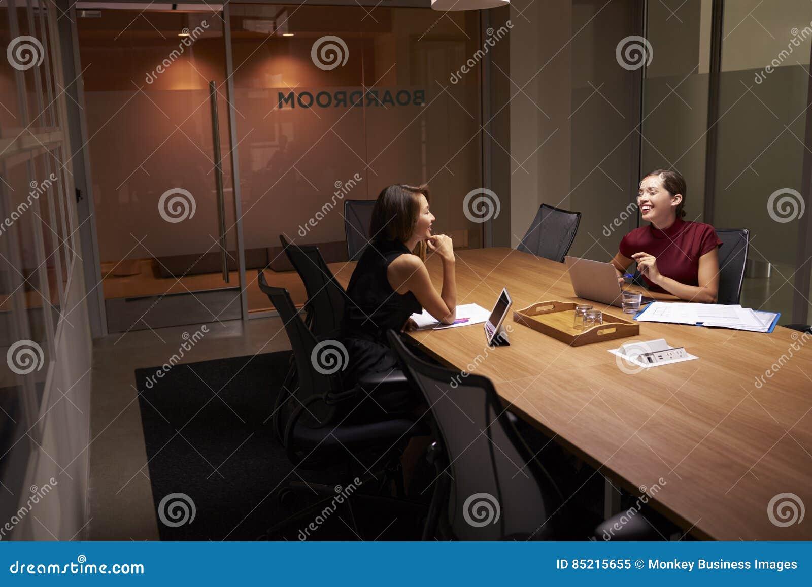 Twee onderneemsters die laat in een bureauaandeel een grap werken