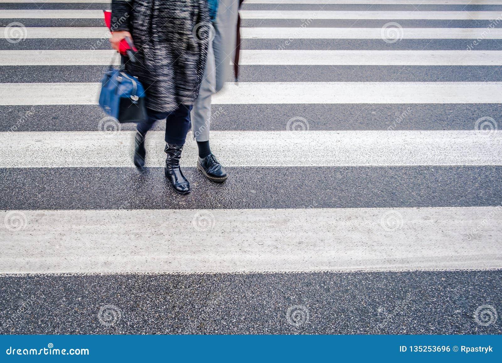 Twee onherkenbare personen in zwarte schoenen kruisen natte straat na regen op zebrapad, rode paraplu, parallelle lijnen
