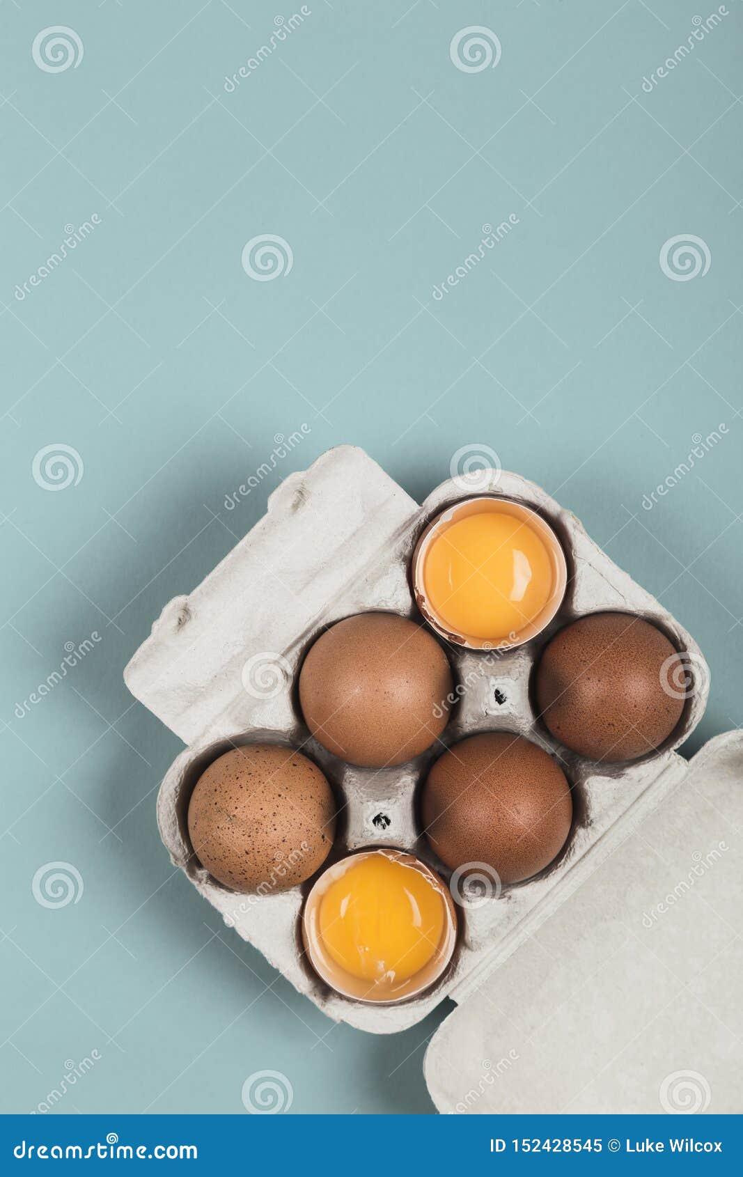 Twee open en vier ongebroken eieren in een eidoos