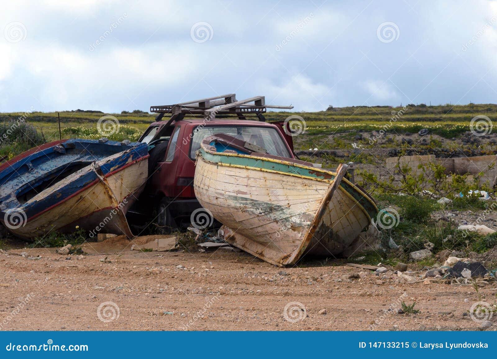 Twee oude verlaten vissersboten en een rode gesloopte auto in een huisvuilstortplaats Verlaten dingen vervoer