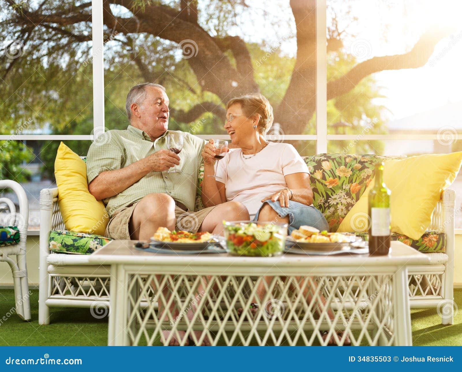 Twee oudsten die diner op terras hebben.