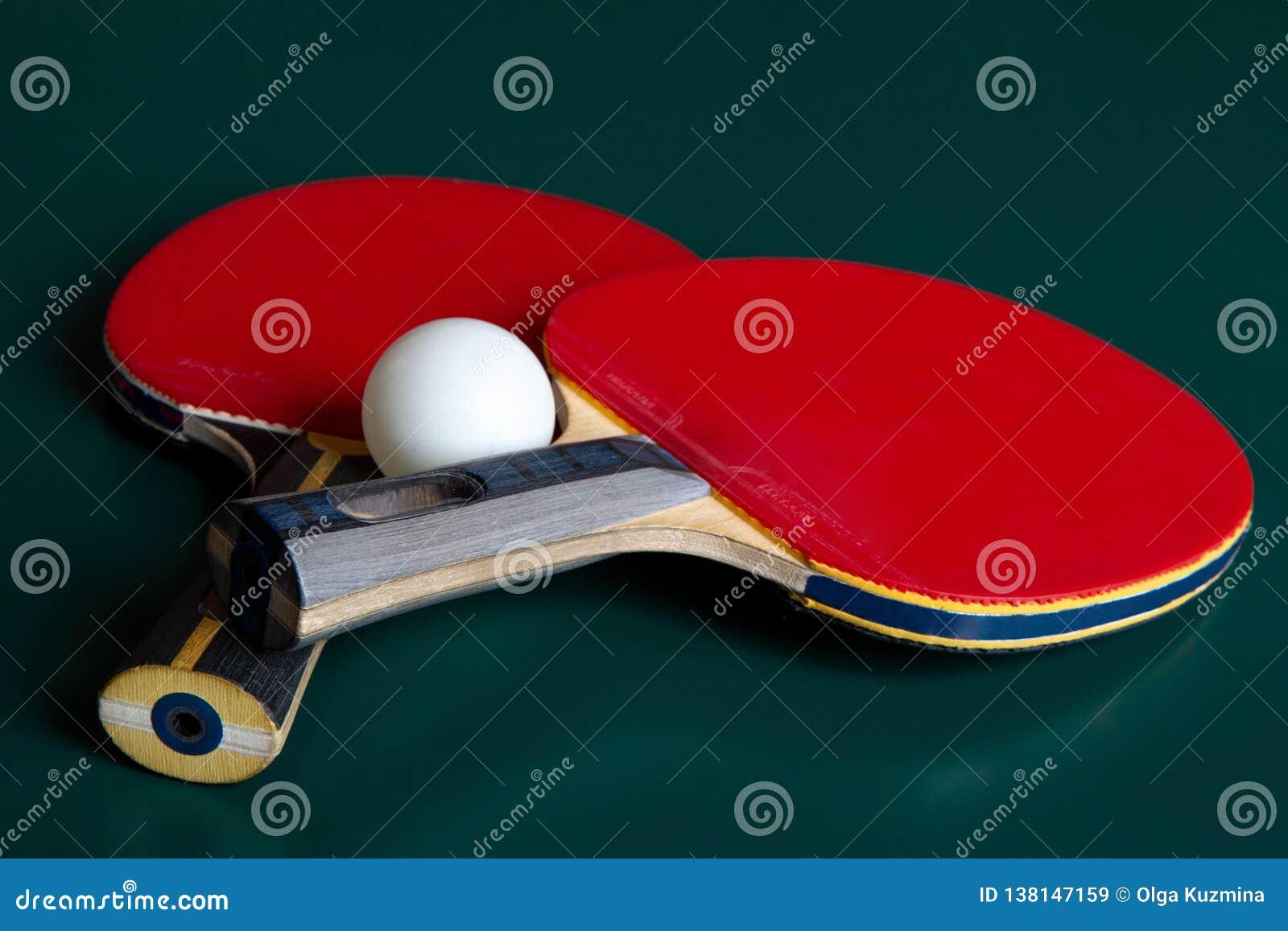 Twee pingpongrackets en een bal op een groene lijst