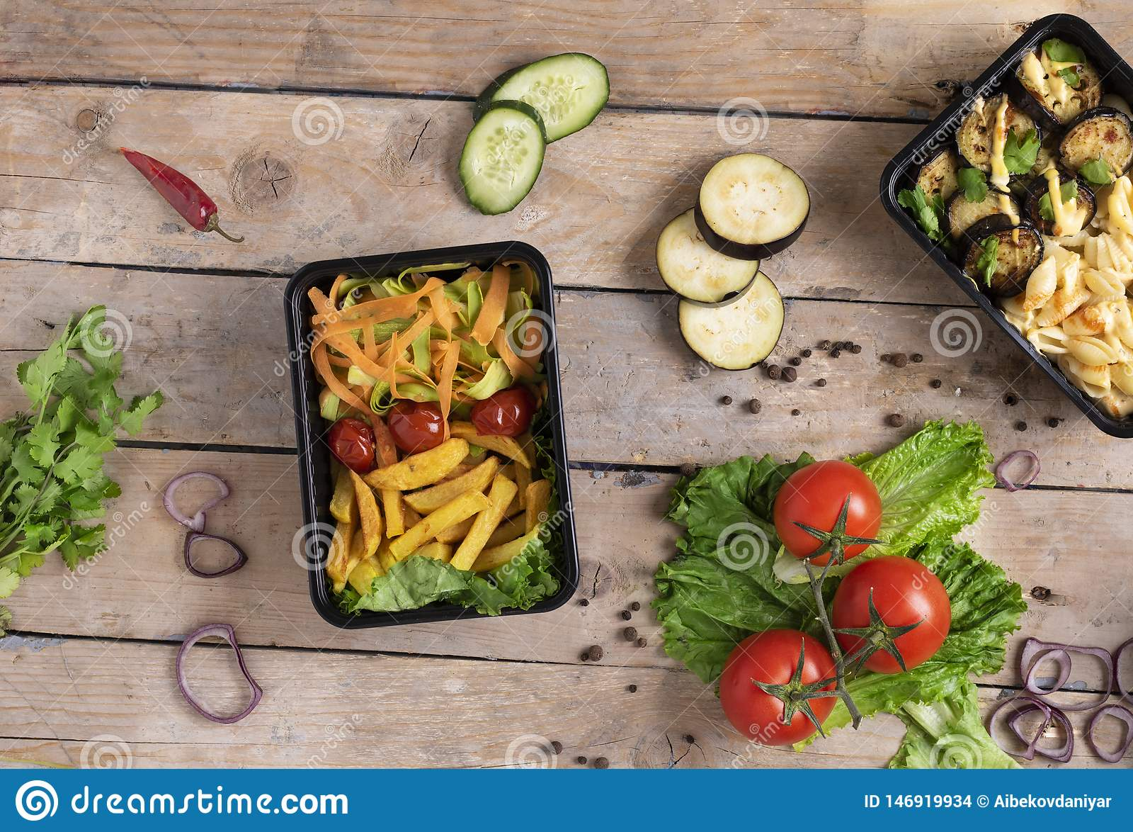 Twee plastic containers met geroosterde kippenvleugels en rauwe groenten op rustieke achtergrond, groentensalade en micro- greens