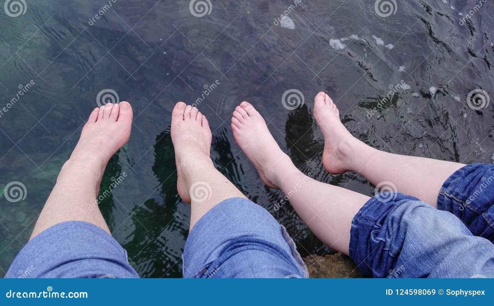 Twee reeksen voeten die over het overzees, Kroatië bengelen
