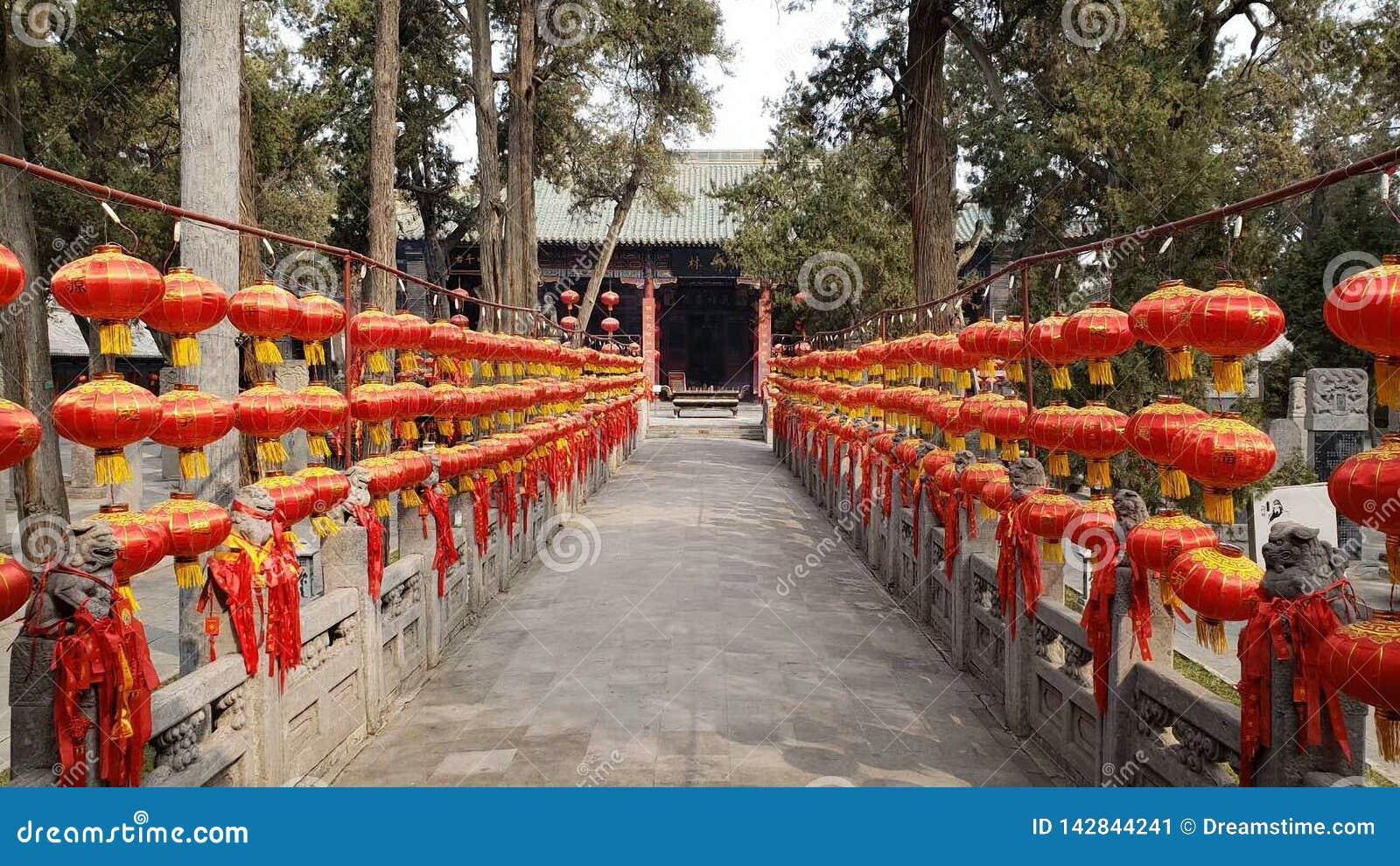 Twee rijen van steenleeuwen in Guanlin-Tempel zijn behandeld met rode lantaarns