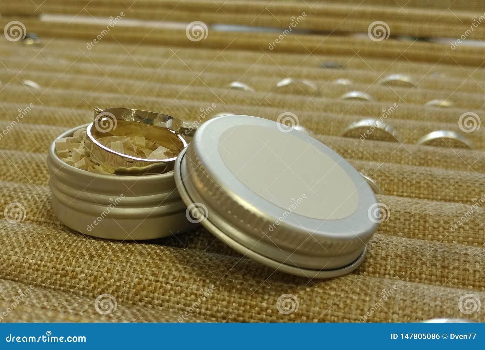 Twee ringen van witgoud zijn in een ronde metaaldoos Tegen de achtergrond van pallets van andere juwelen