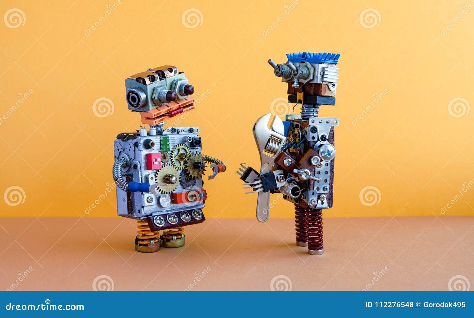 Twee robotsmededeling, machine het leren concept Robotachtige karakters, regelbare moersleutelmoersleutel Gele bruine muur,