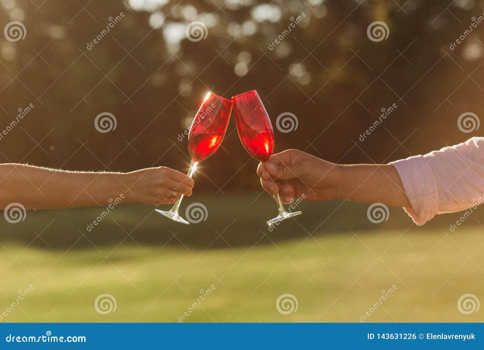 Twee rode wijnglazen in vrouwenhand en man hand op aardachtergrond