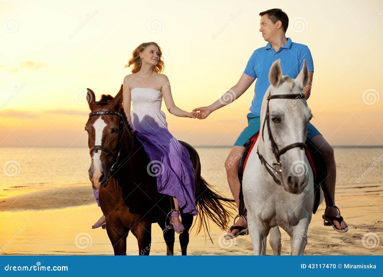 Twee ruiters op horseback bij zonsondergang op het strand De minnaars berijden hors