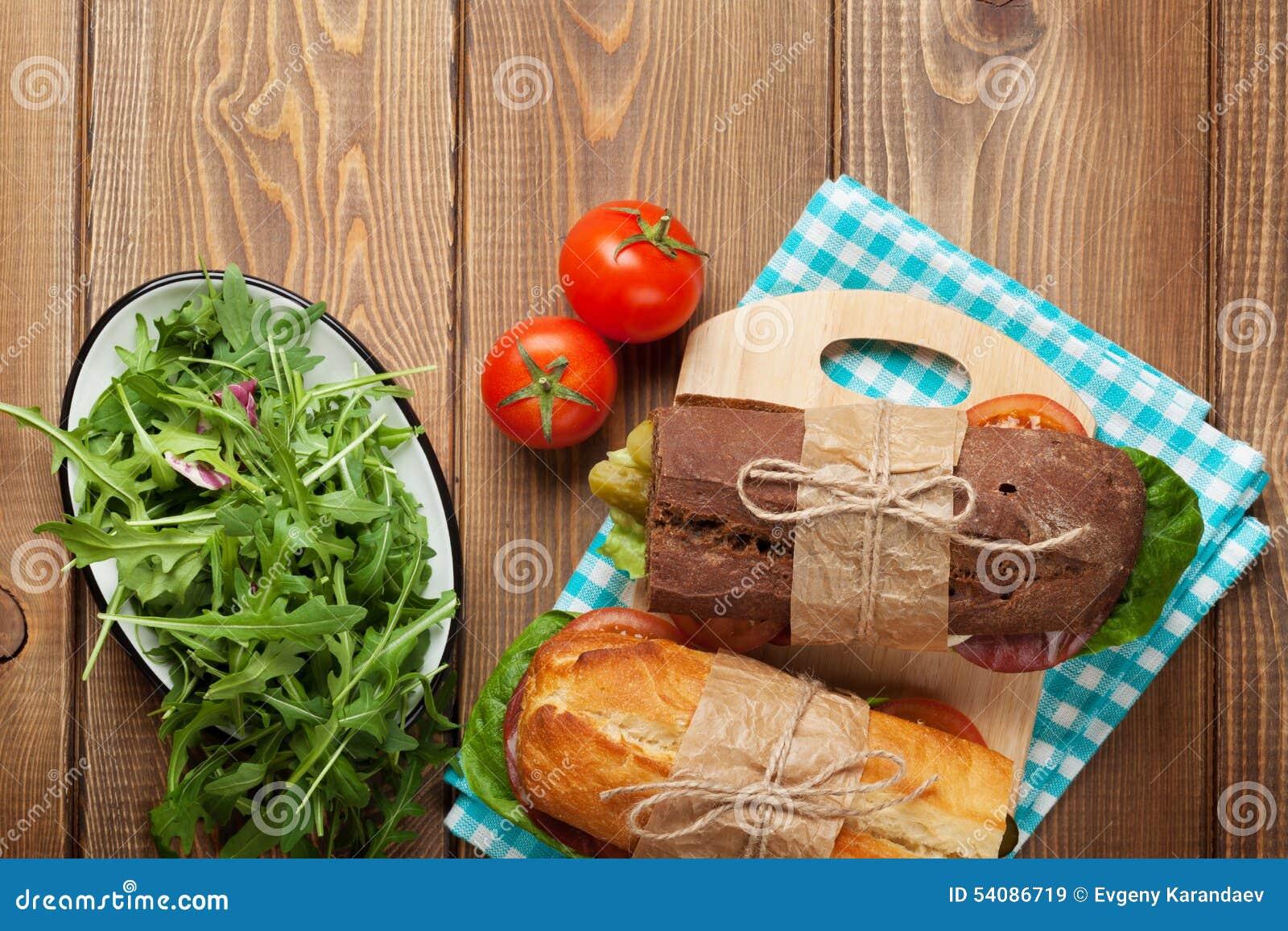 Twee sandwiches met salade, ham, kaas