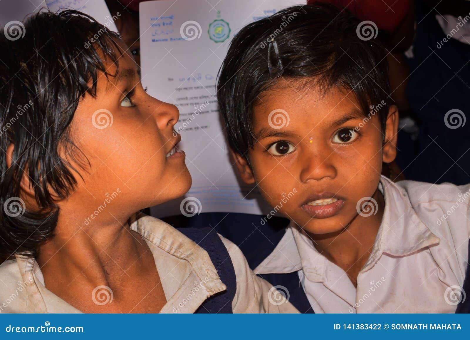 Twee schoolmeisjes van een landelijke lage school van Bengalen, keken naar de cameralens