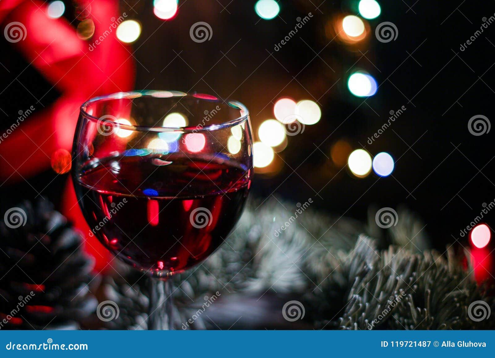 Twee steekt het rode wijnglas tegen Kerstmis decoratieachtergrond, vooravond van aan Kerstmis