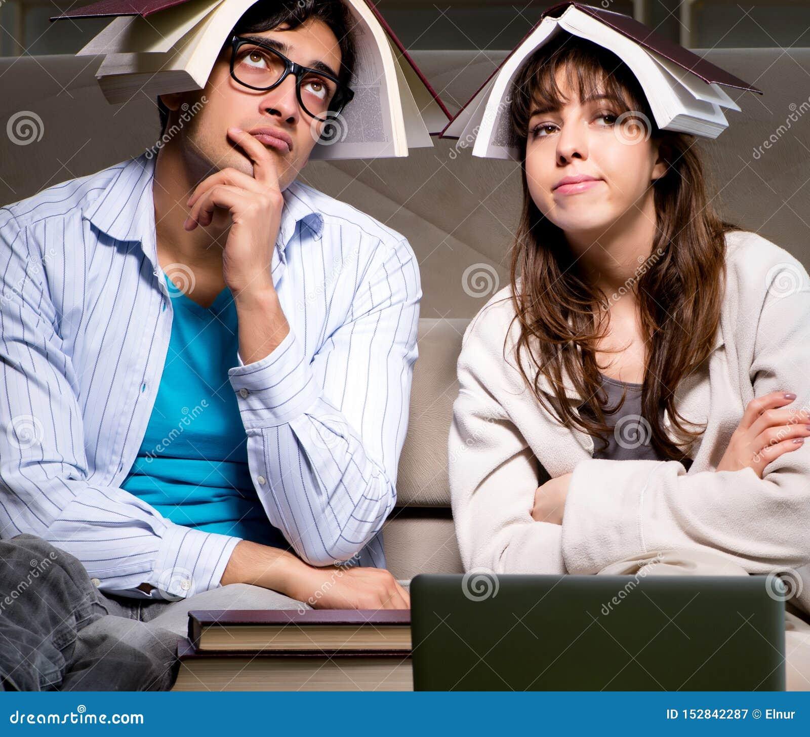 Twee studenten die laat het voorbereidingen treffen voor examens bestuderen