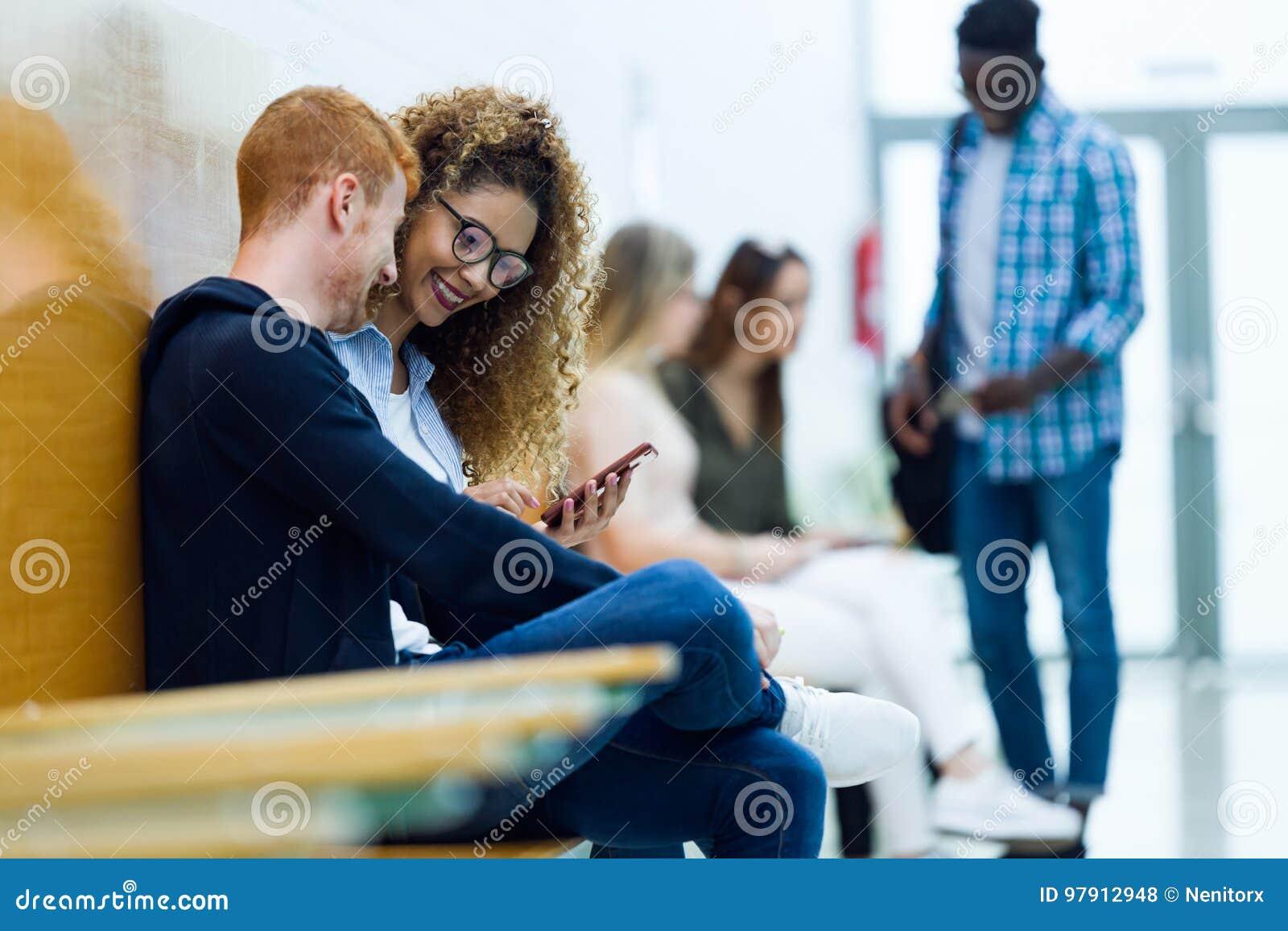 Twee studenten die zij mobiele telefoon op een universiteit gebruiken