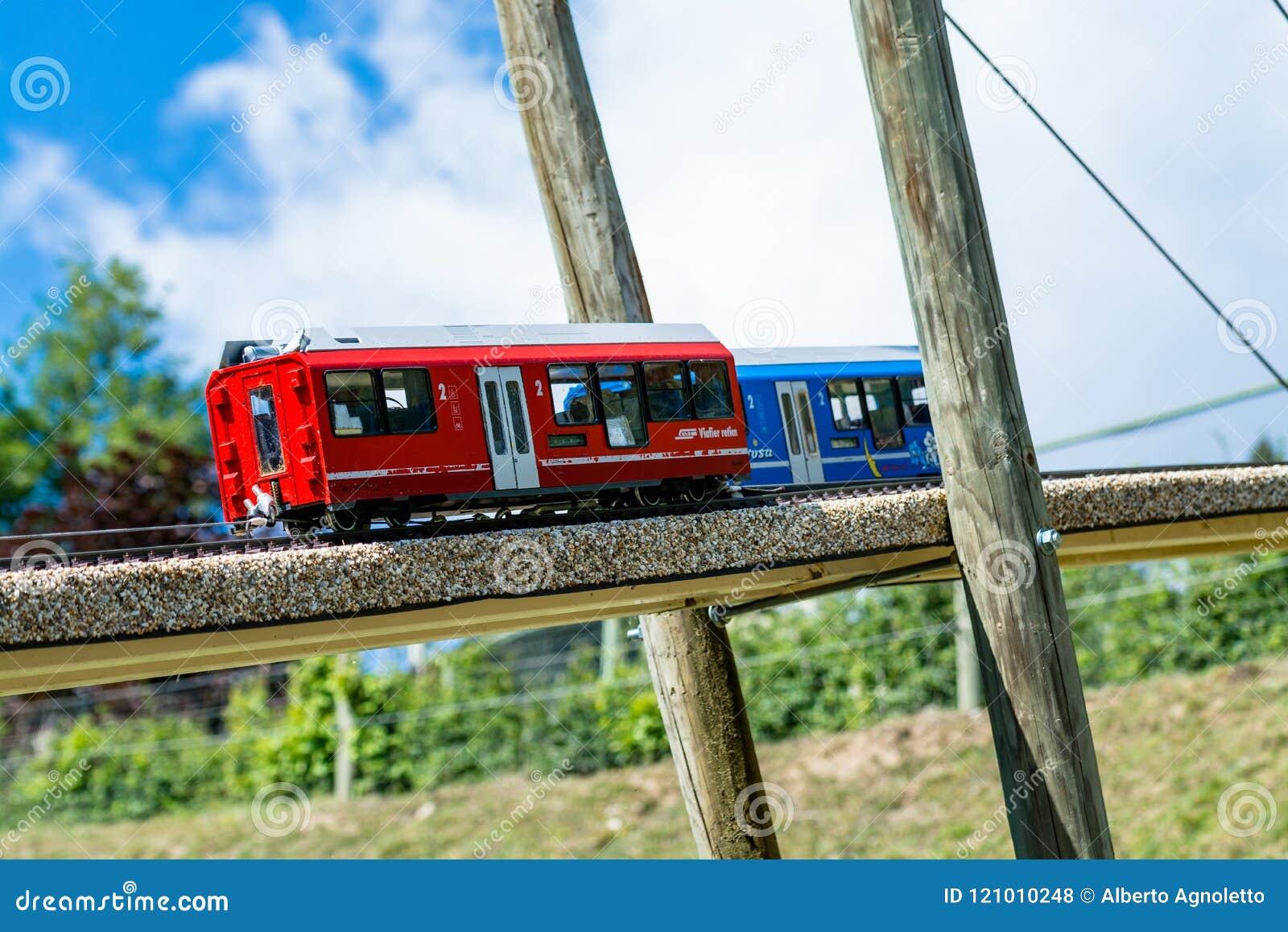 Twee stuk speelgoed locomotieven, één blauw en één rood, op een houten brug
