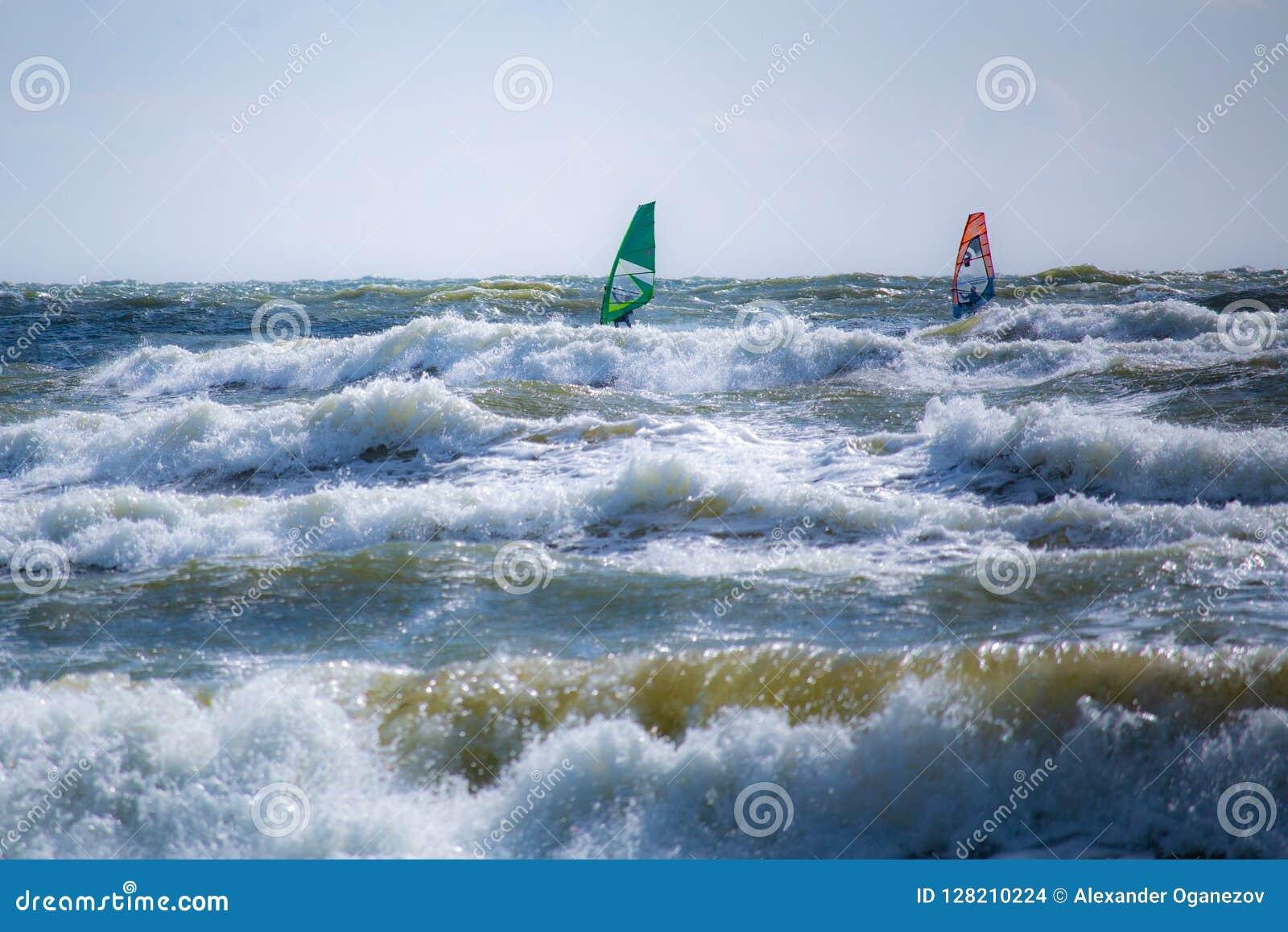 Twee surfers op stormachtige Oostzee in Litouwen