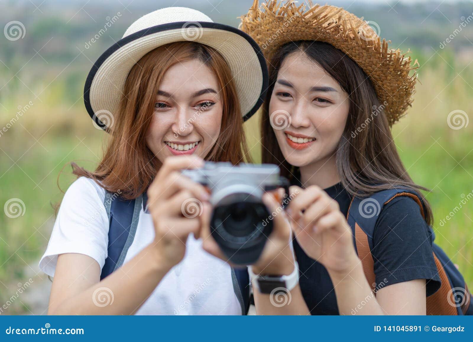 Twee toeristenvrouw die een foto met camera in aard nemen