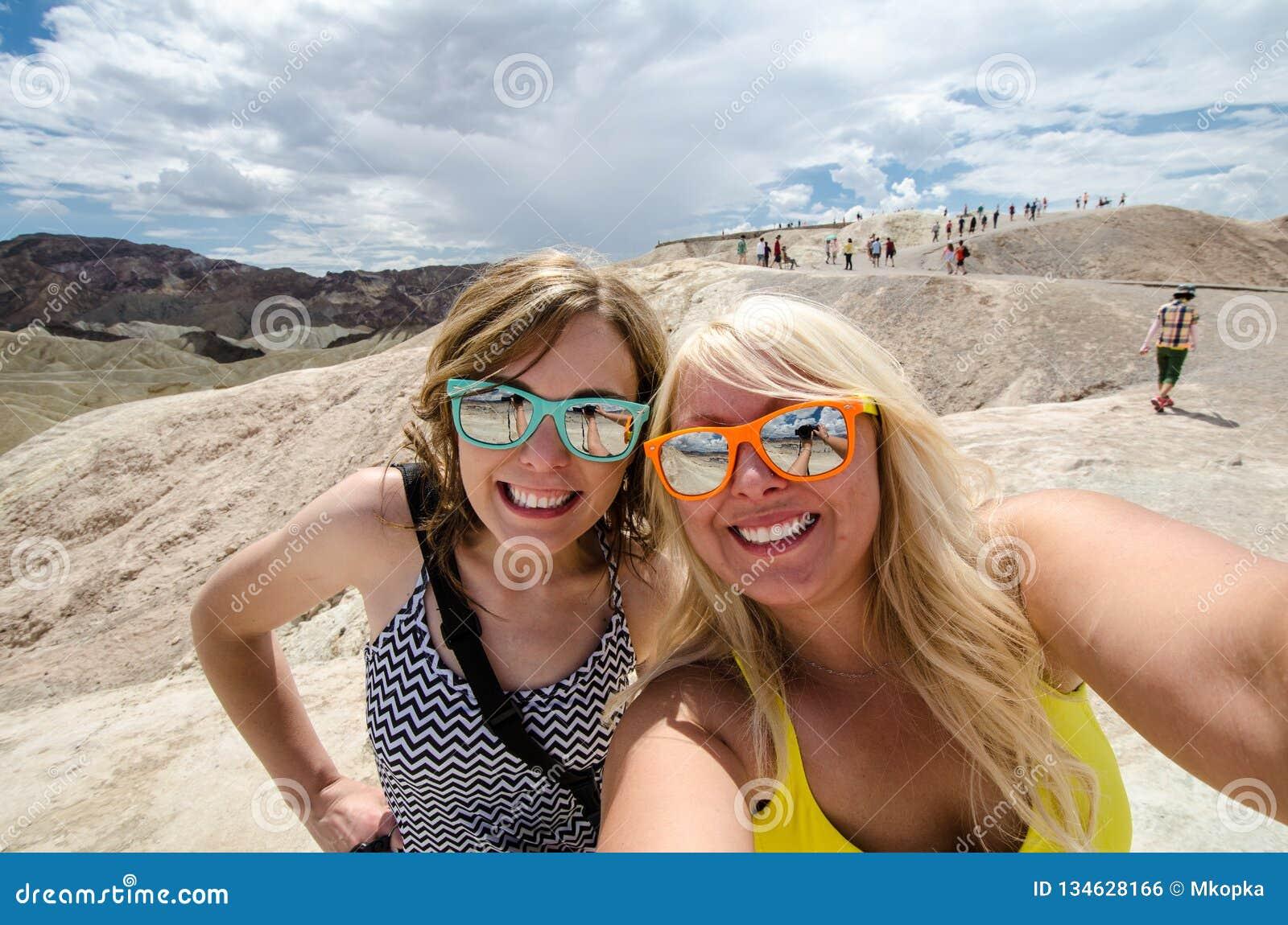 Twee volwassen wijfjes nemen een selfie terwijl bij Zabriskie-Puntvooruitzicht in van de de Doodsvallei van Californië het Nation