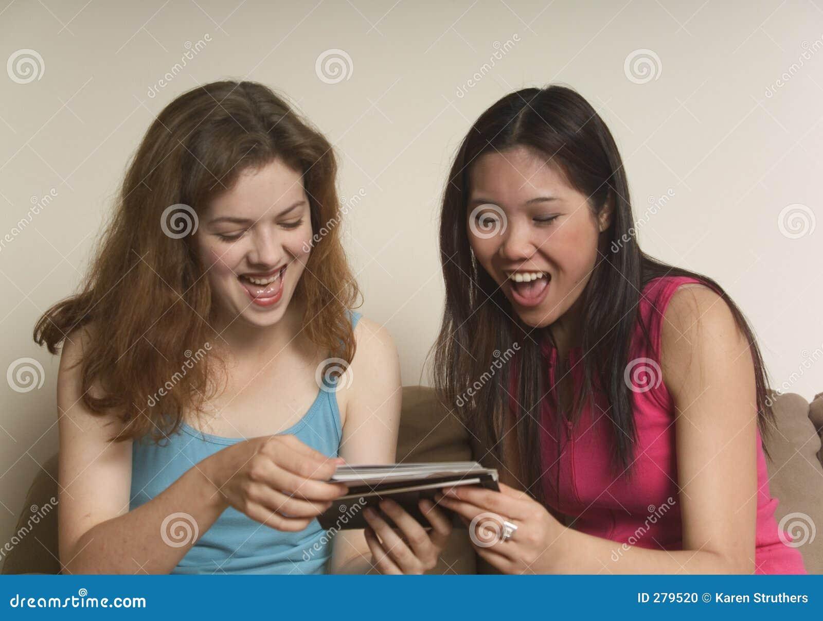 Twee vrienden die bij foto s lachen