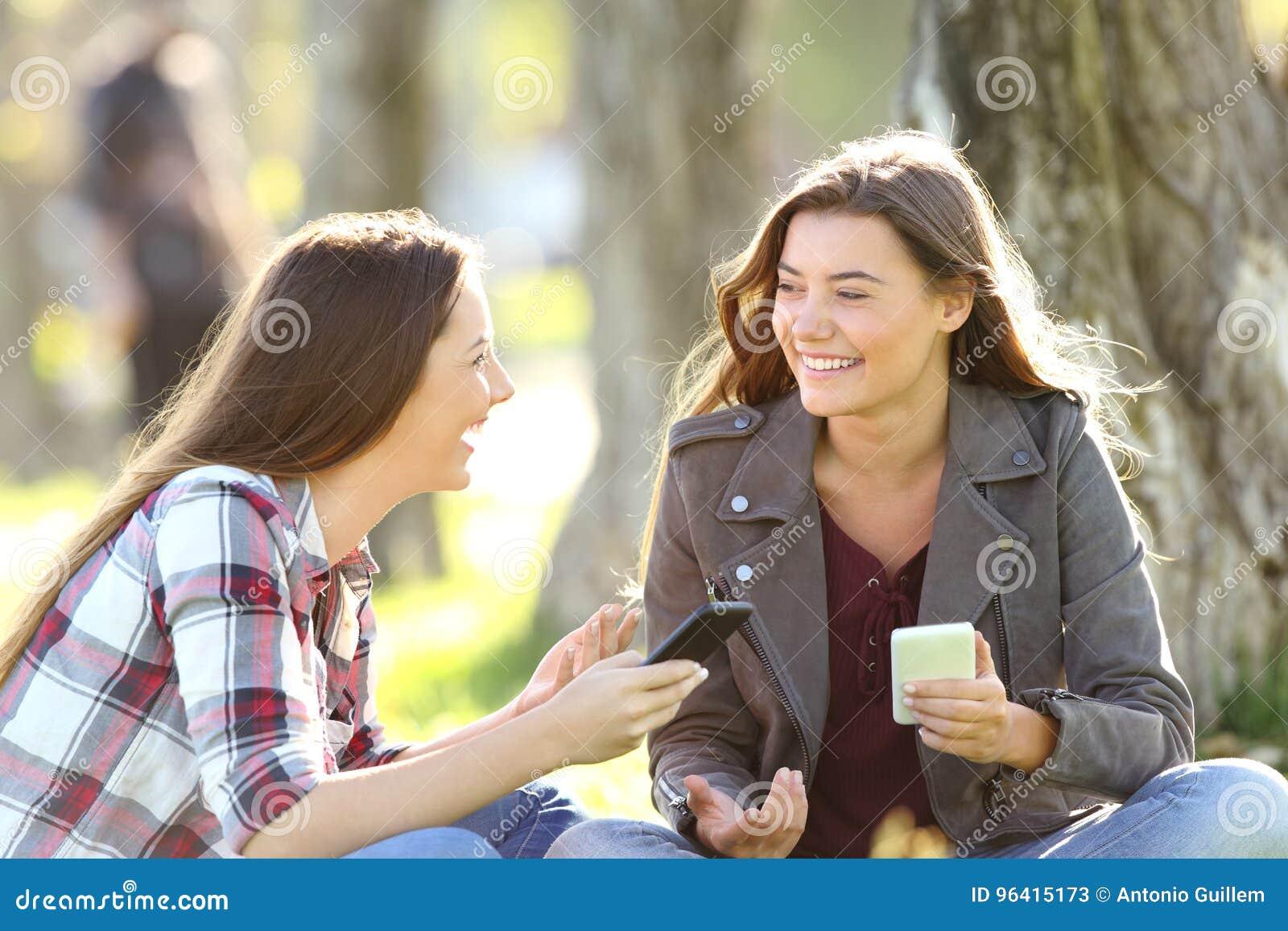 Twee vrienden die houdend hun slimme telefoons spreken