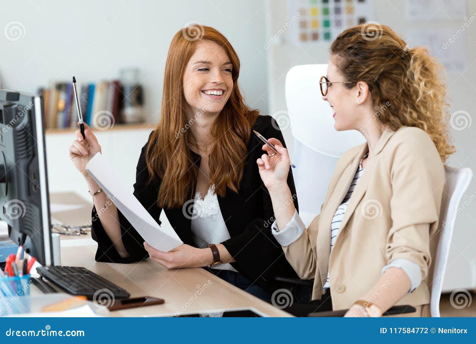 Twee vrij het jonge bedrijfsvrouw spreken en het herzien documenten in het bureau
