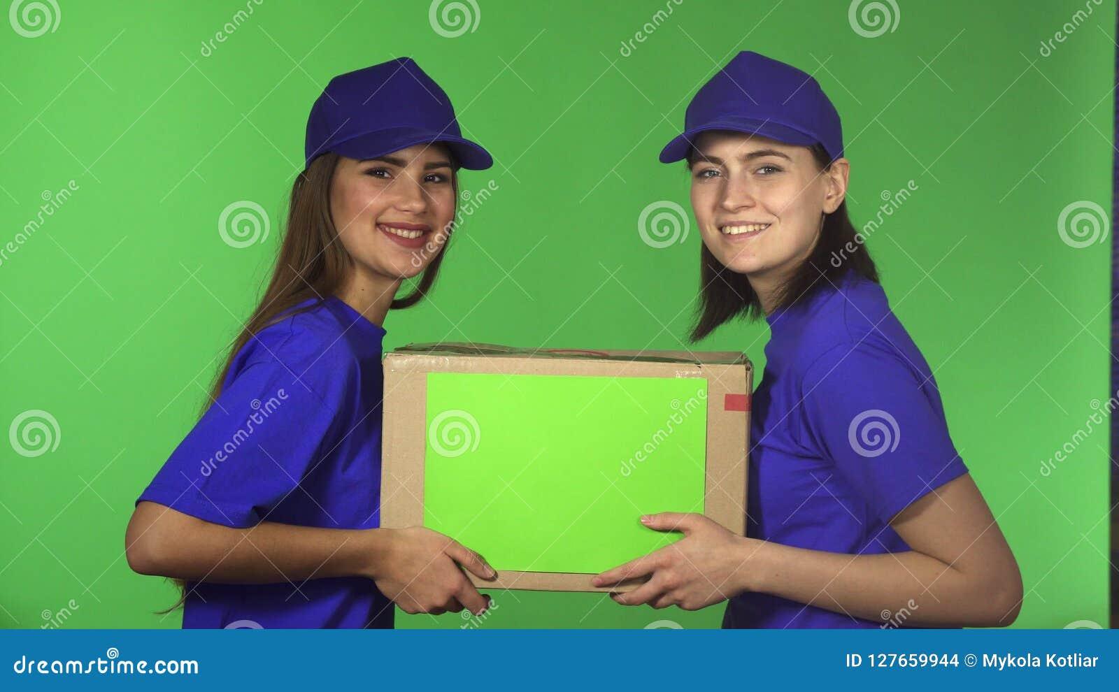 Twee vrolijke vrouwelijke arbeiders die van de leveringsdienst de doos van het holdingskarton glimlachen