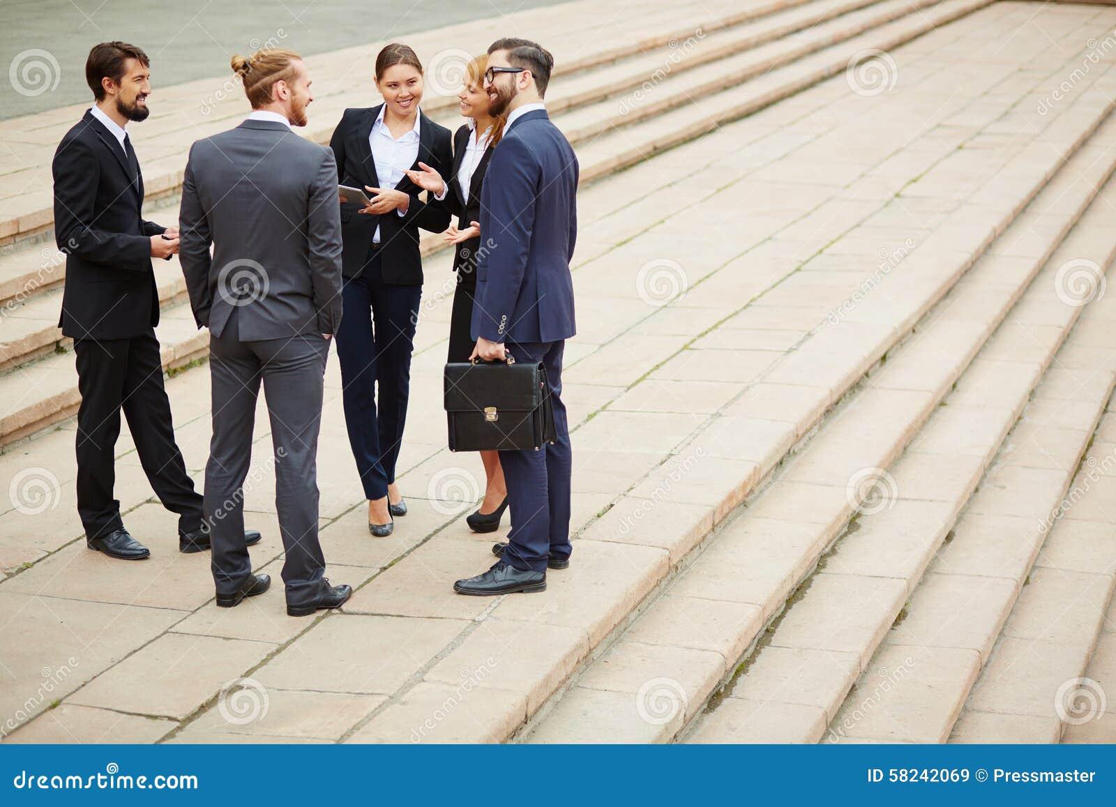 Twee vrolijke zakenlieden die over zaken spreken terwijl één van hen die computermonitor richten