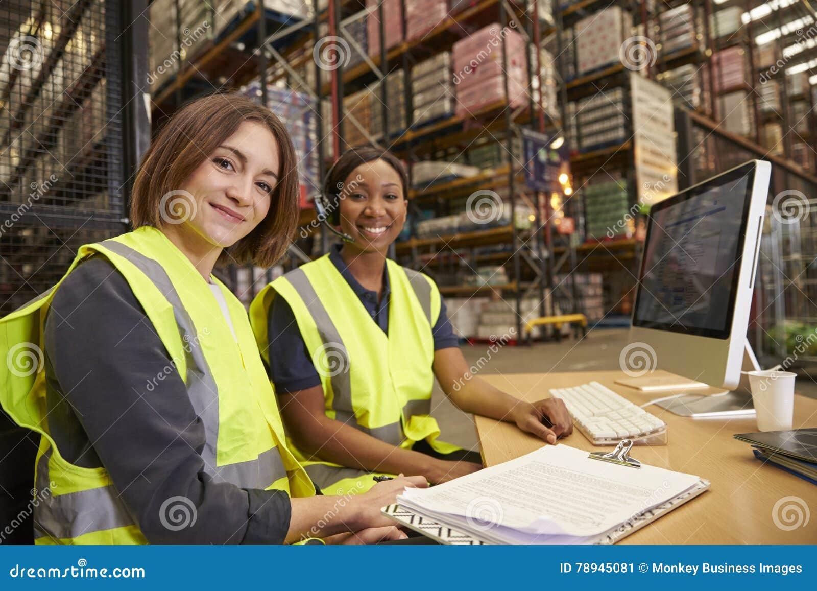 Twee vrouwelijke collega s in een pakhuisbureau kijken aan camera